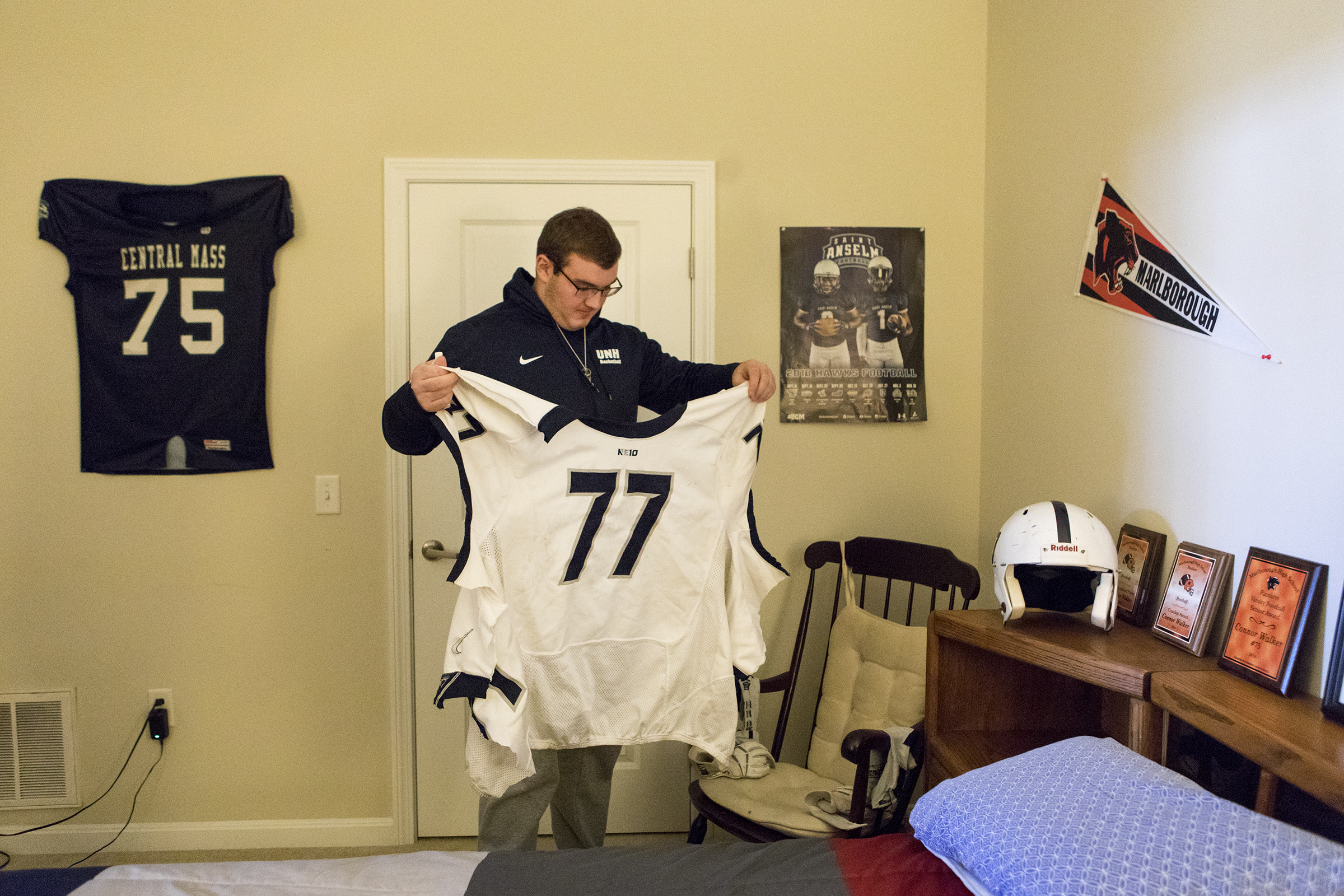 For the first time, Connor looks at the Saint Anselm College football jersey that had to be cut off of him when he sustained his spinal cord injury in his room at his family home in Marlborough on Oct. 25, 2018.