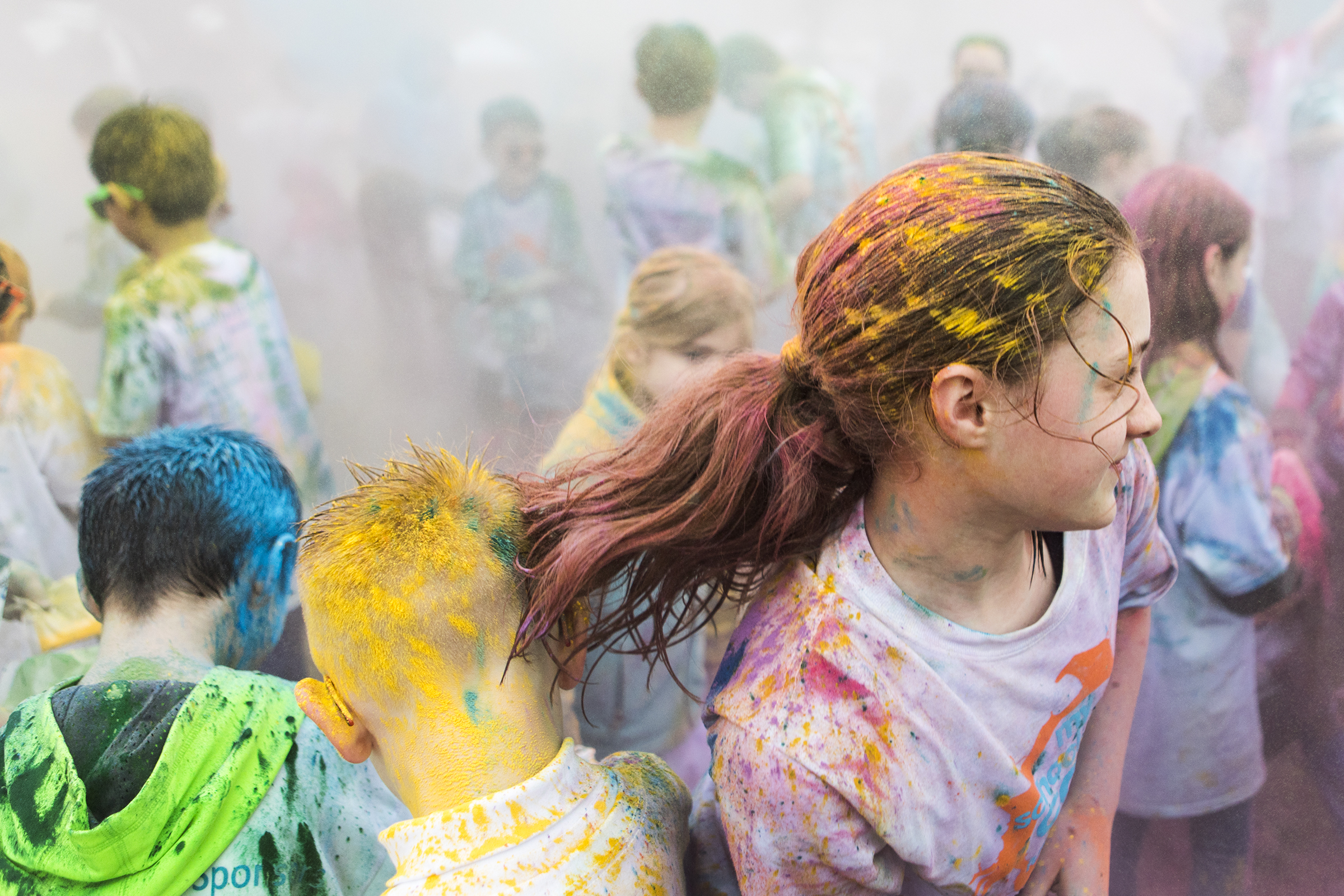 Runners throw color packets during the Color Run at the Kennedy Elementary School on April 29, 2018.