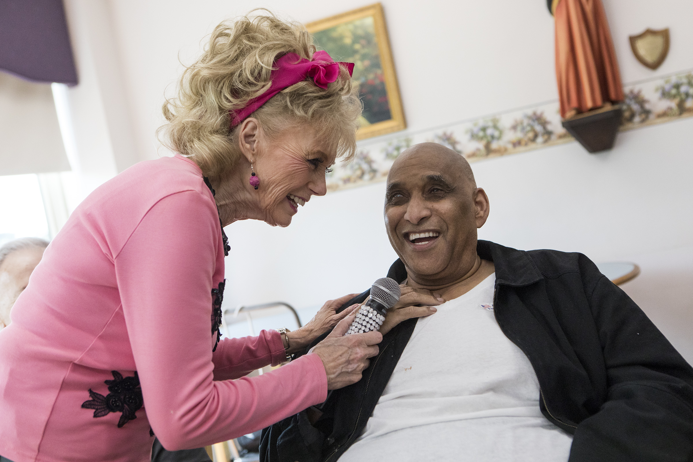 Fran Owens sings with resident Howard Wigfall, of Cambridge, during an entertainment hour at Sancta Maria Nursing Facility in Cambridge on Aug. 30, 2018.