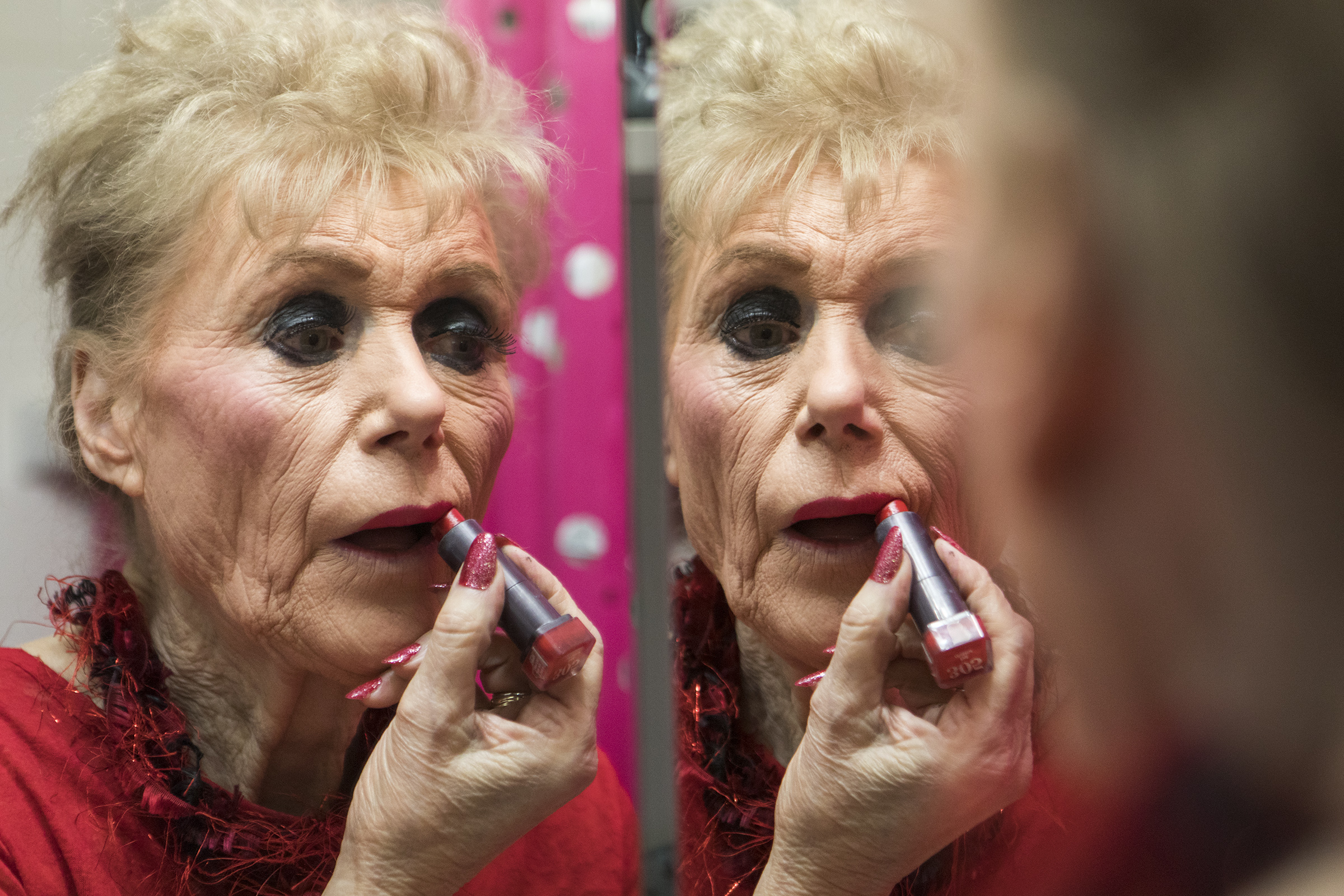 Fran Owens applies lipstick in the bathroom of her home in Stoneham on Dec. 7, 2018. Owens describes her makeup routine as transforming from a caterpillar to a butterfly.