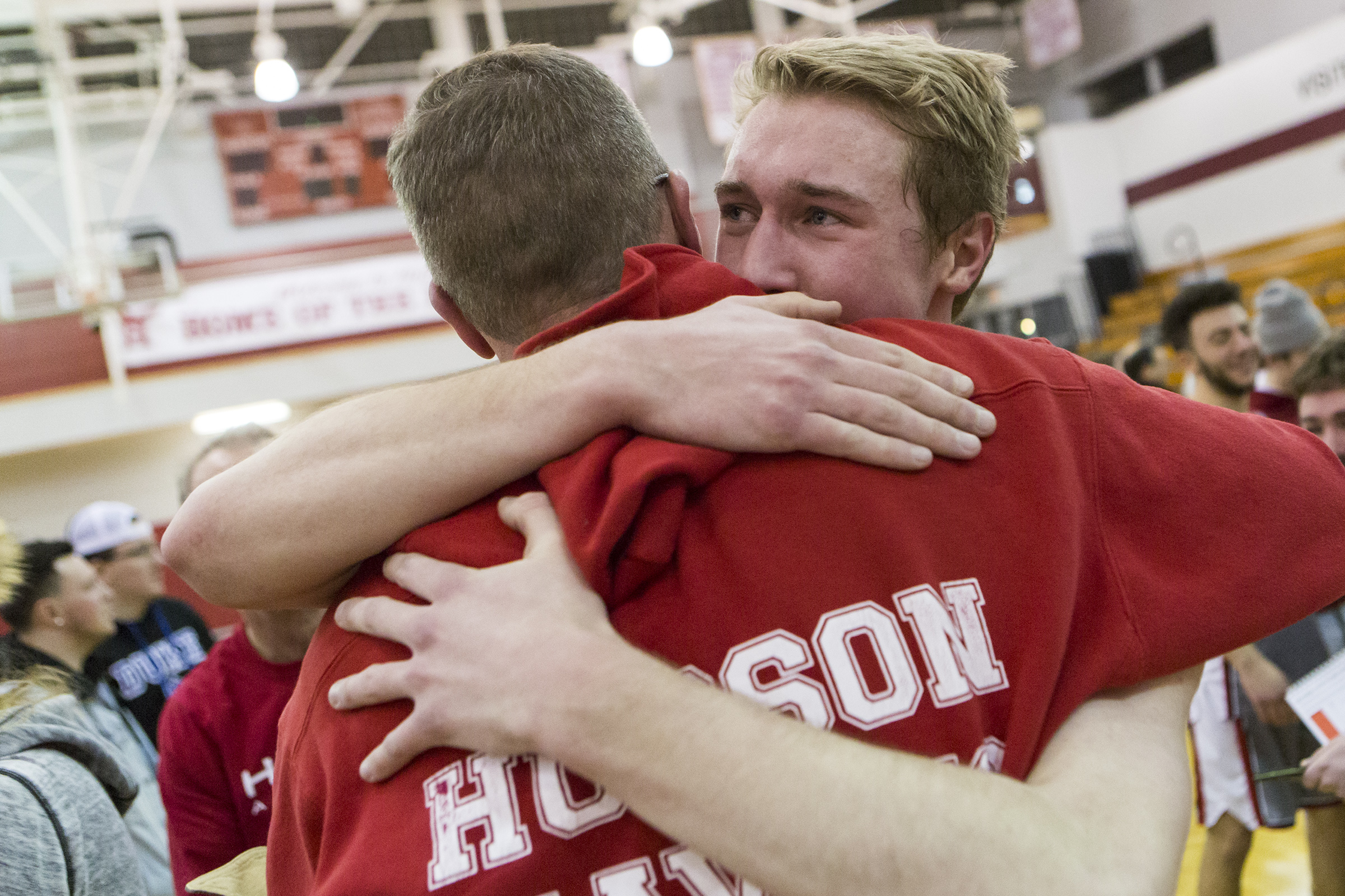 Hudson senior captain Tim Person hugs his father Rich Person after scoring his 1000th career point during the game against Gardner in Hudson on Feb. 26, 2019.