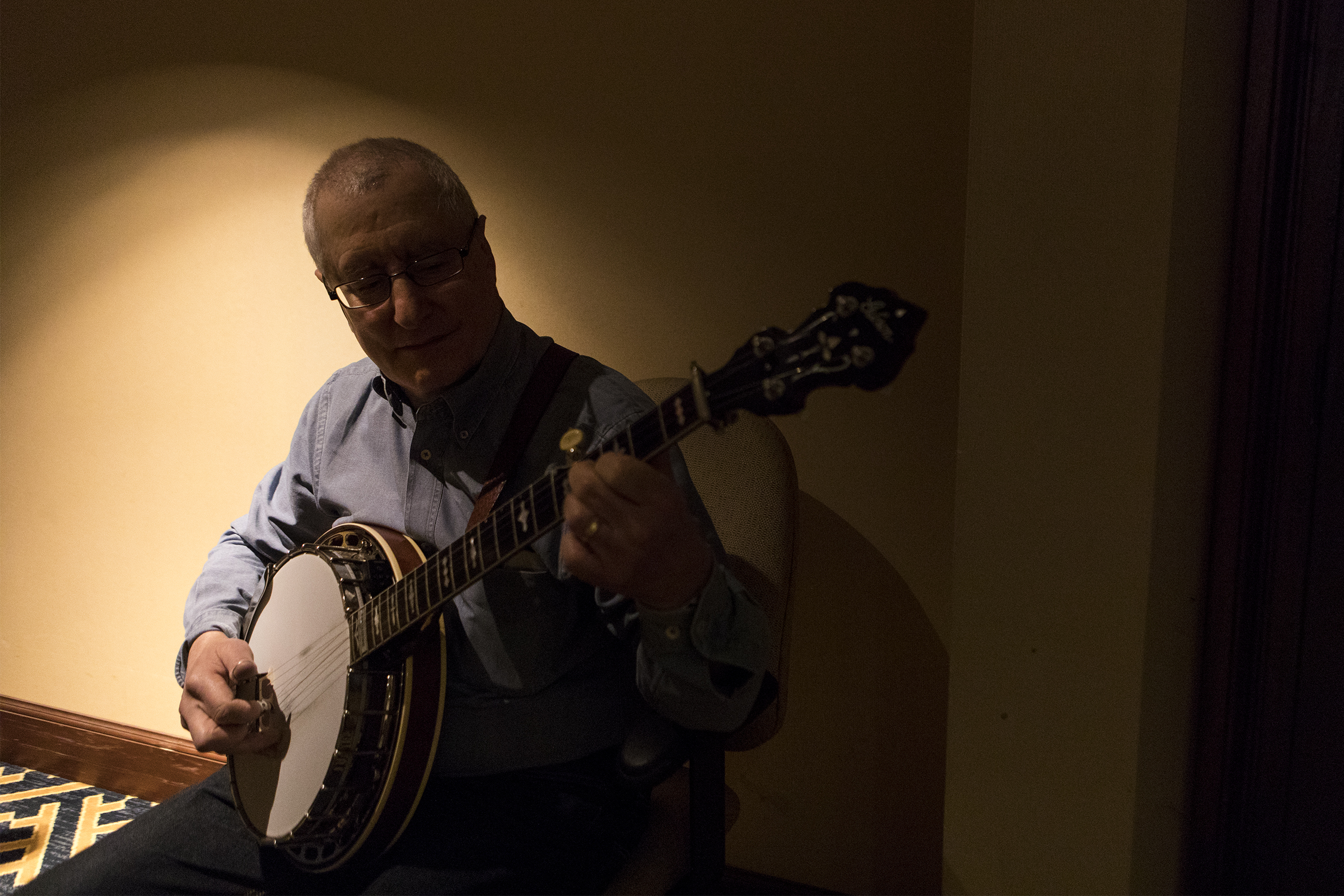 David Hollender, professor at Berklee College of Music, plays the banjo in the hallway during the annual Joe Val Bluegrass Festival at the Sheraton in Framingham on Feb. 16, 2019.