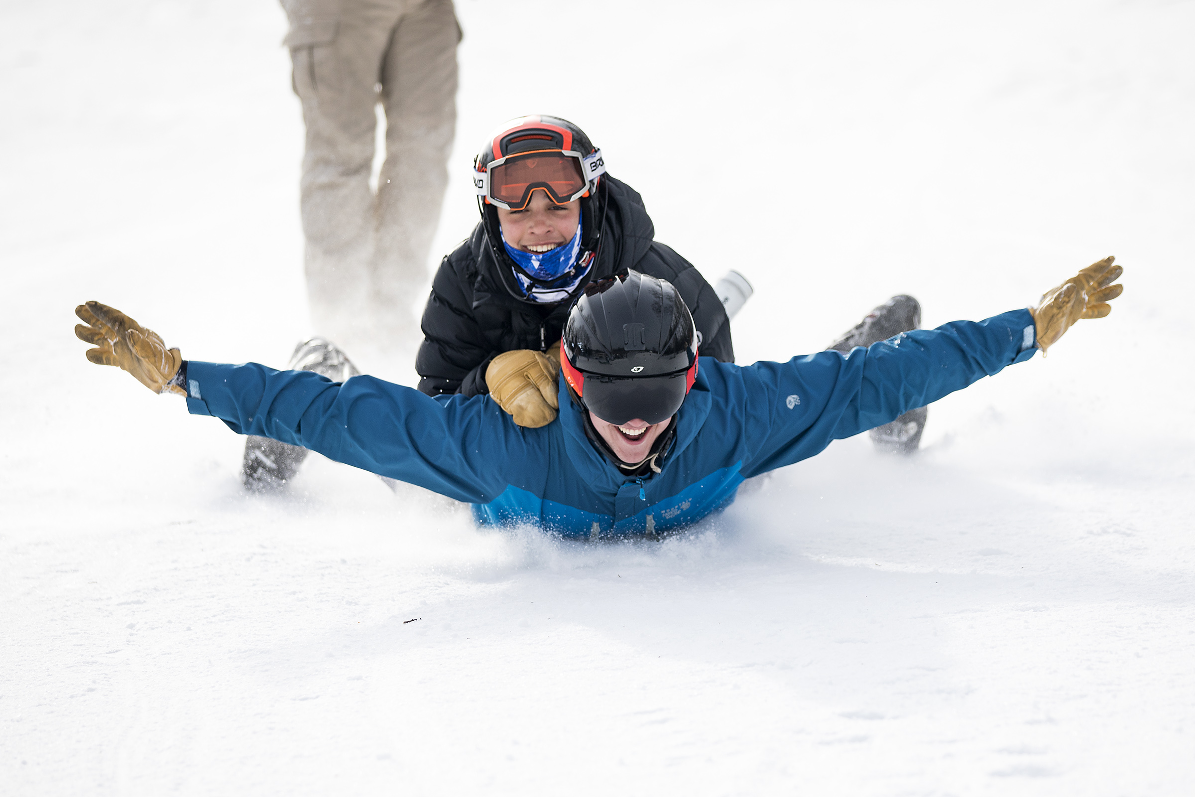 Natick senior Jay Sant uses a lunch tray to sled with freshman Josh Libby on his back during the Alpine State Championship at Wachusett Mountain Ski Area on Feb. 27, 2019.