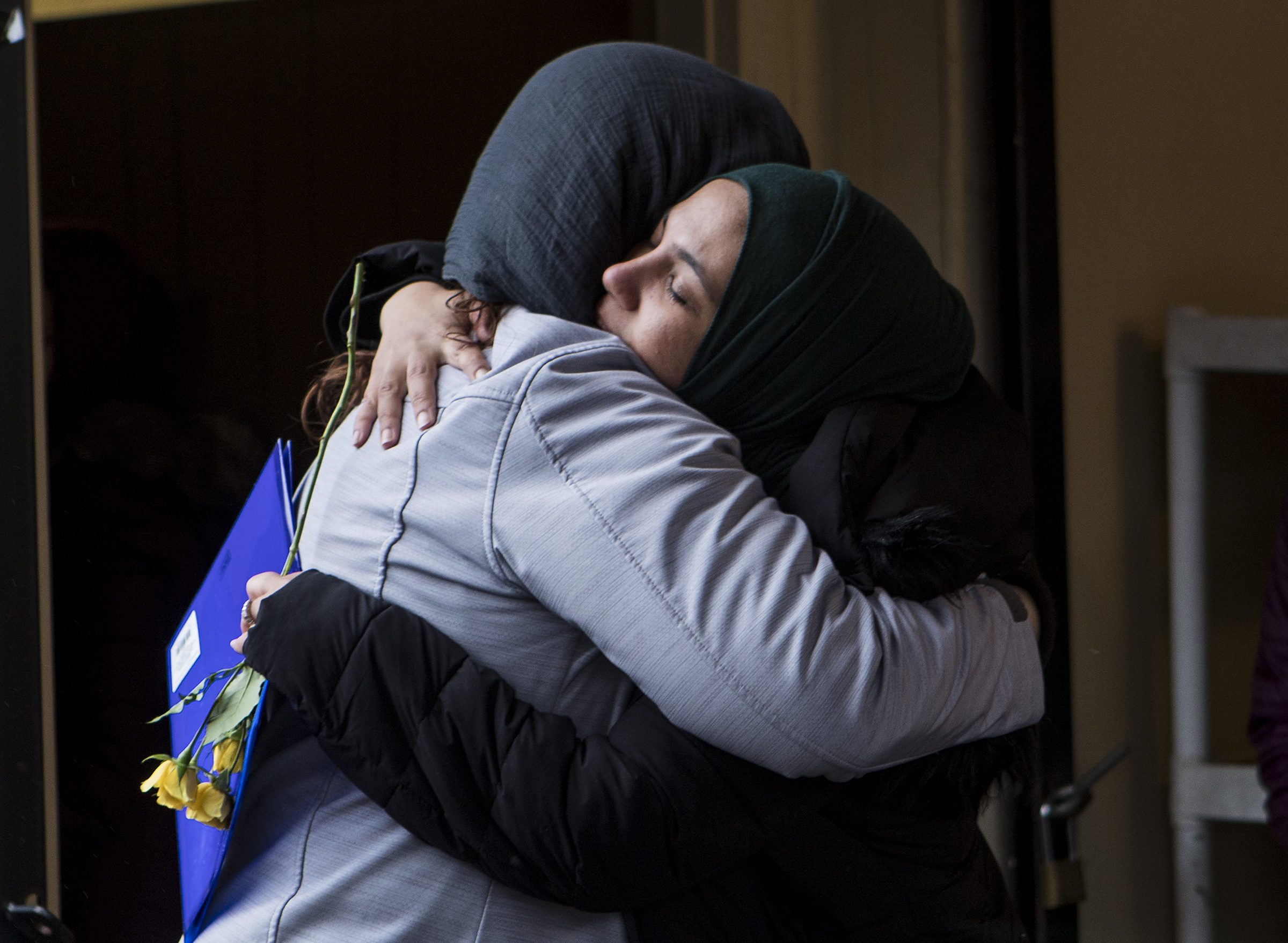 Amber Iqbal, of Lexington, right, receives a hug from interfaith supporter Carla Bradford, of Bedford, before entering the Islamic Center of Burlington for Jumu'ah on March 22, 2019