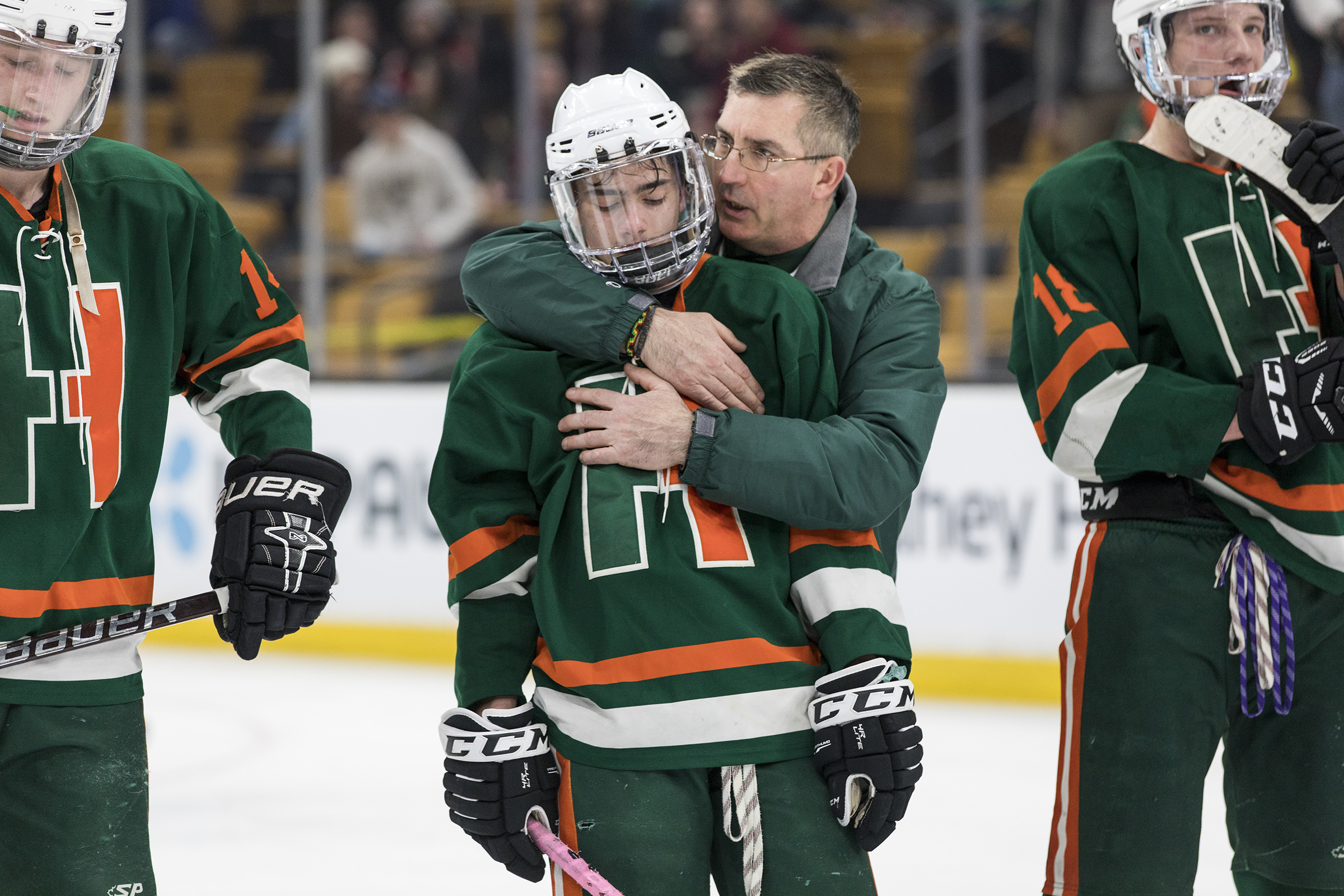 Hopkinton assistant coach Scott O'Connor hugs junior Kyle Rogers after the Mountaineers of Wachusett Regional defeated the Hillers, 3-2, in the Division 3 state championship game at the TD Garden in Boston, March 17, 2019