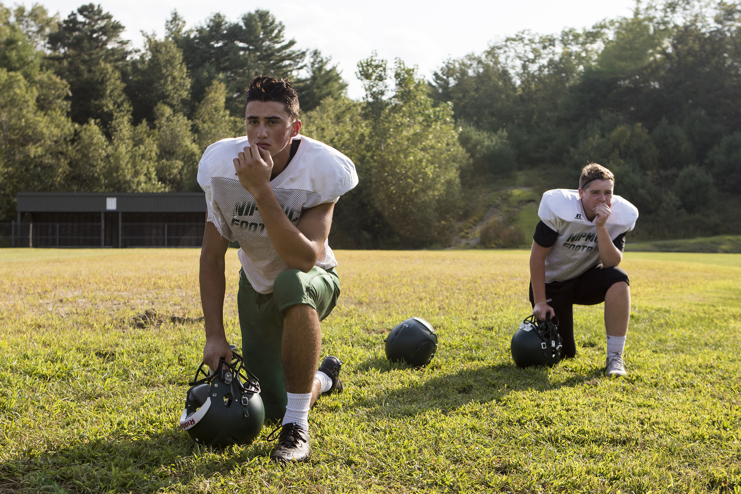 Nipmuc junior Nate Gould, left, and sophomore Joey Leclaire take a knee after their senior captain was injured during football practice at Nipmuc Regional High School in Upton on Aug. 24, 2018.