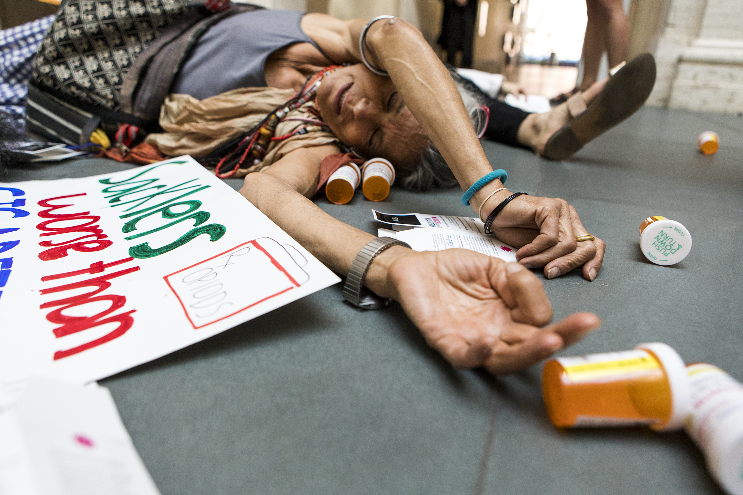 Addiction psychiatrist Annatina Miescher, of New York, lies on the floor during the die-in protesting the Sackler family and their role in perpetuating the opioid epidemic at the Harvard Art Museum on July 20, 2018.