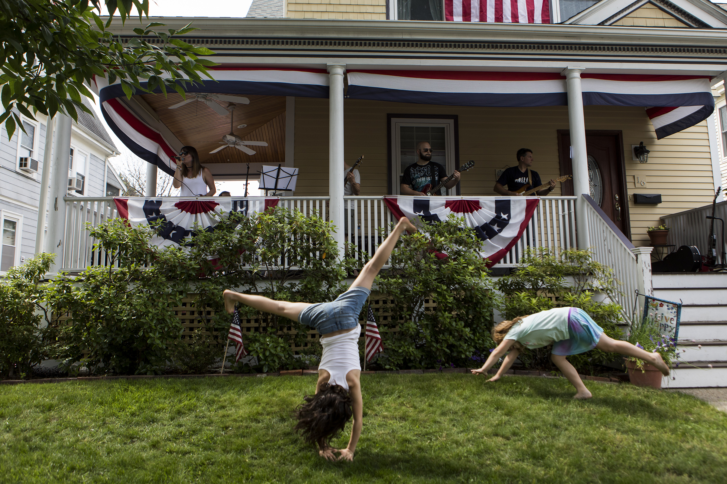 Ruby Quinn, 8, of Medford, left, and Julia McDermott, 7, of Arlington, cartwheel while Second Helping of Slop performs on Cleveland Street during Arlington Porchfest on June 09, 2018.