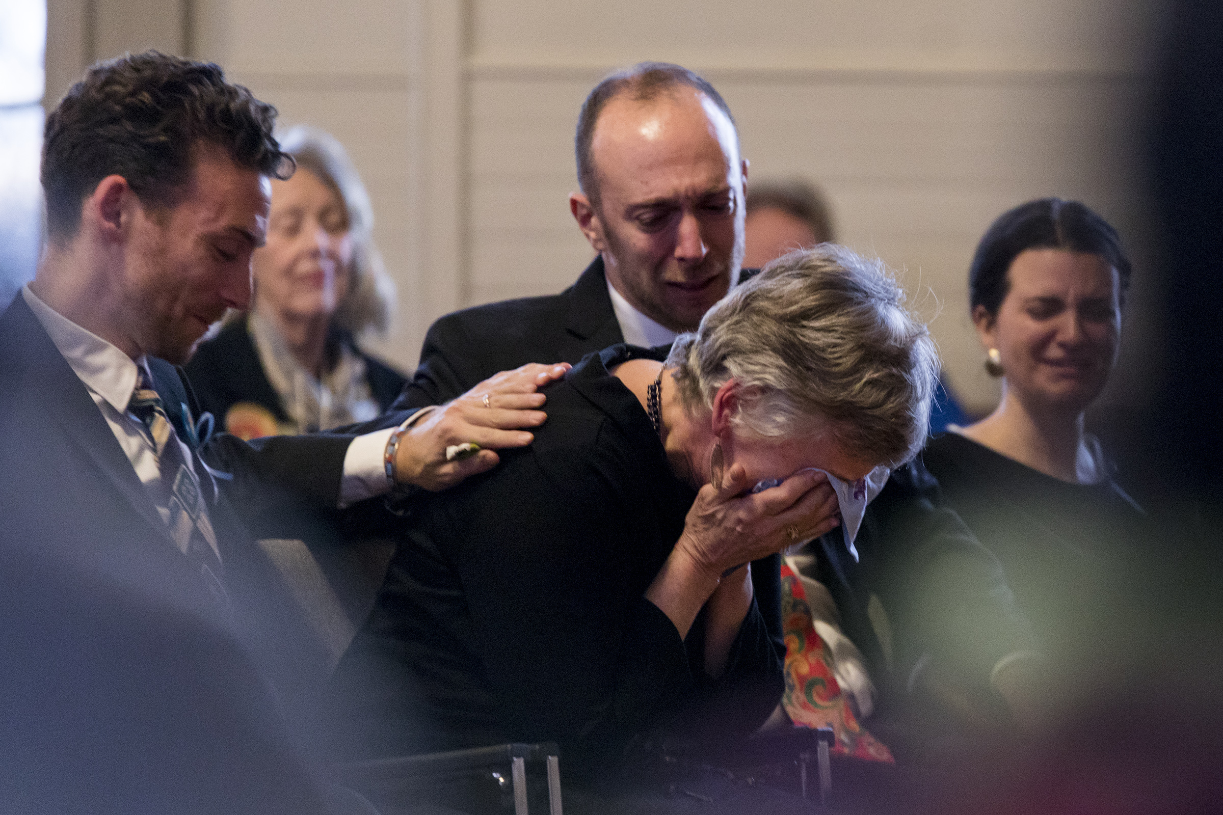 Chris Brumback reacts to hearing her husband's voice on a recorded message while her sons Stephen and Michael Wechsler comfort her during a service to celebrate Bill Wechsler's life at Holliston Town Hall on Nov. 29, 2018. Beloved social worker Wechsler passed away after a nearly three-year battle against ALS.