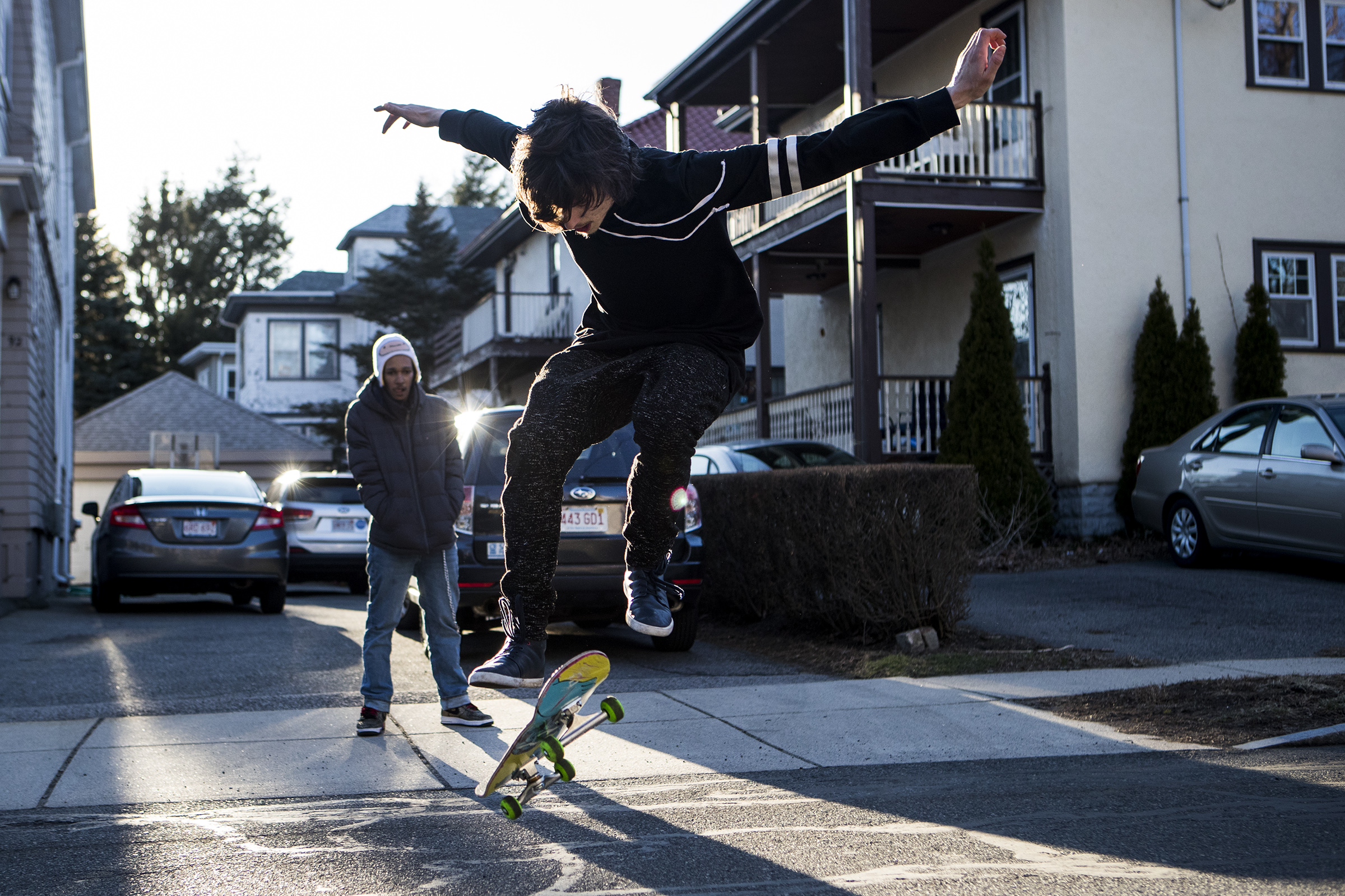 Kairi Thomas, left, watches while Dylan Ross, both of Belmont, skateboards along Oak Ave during a sunny afternoon in Belmont on April 1, 2019.