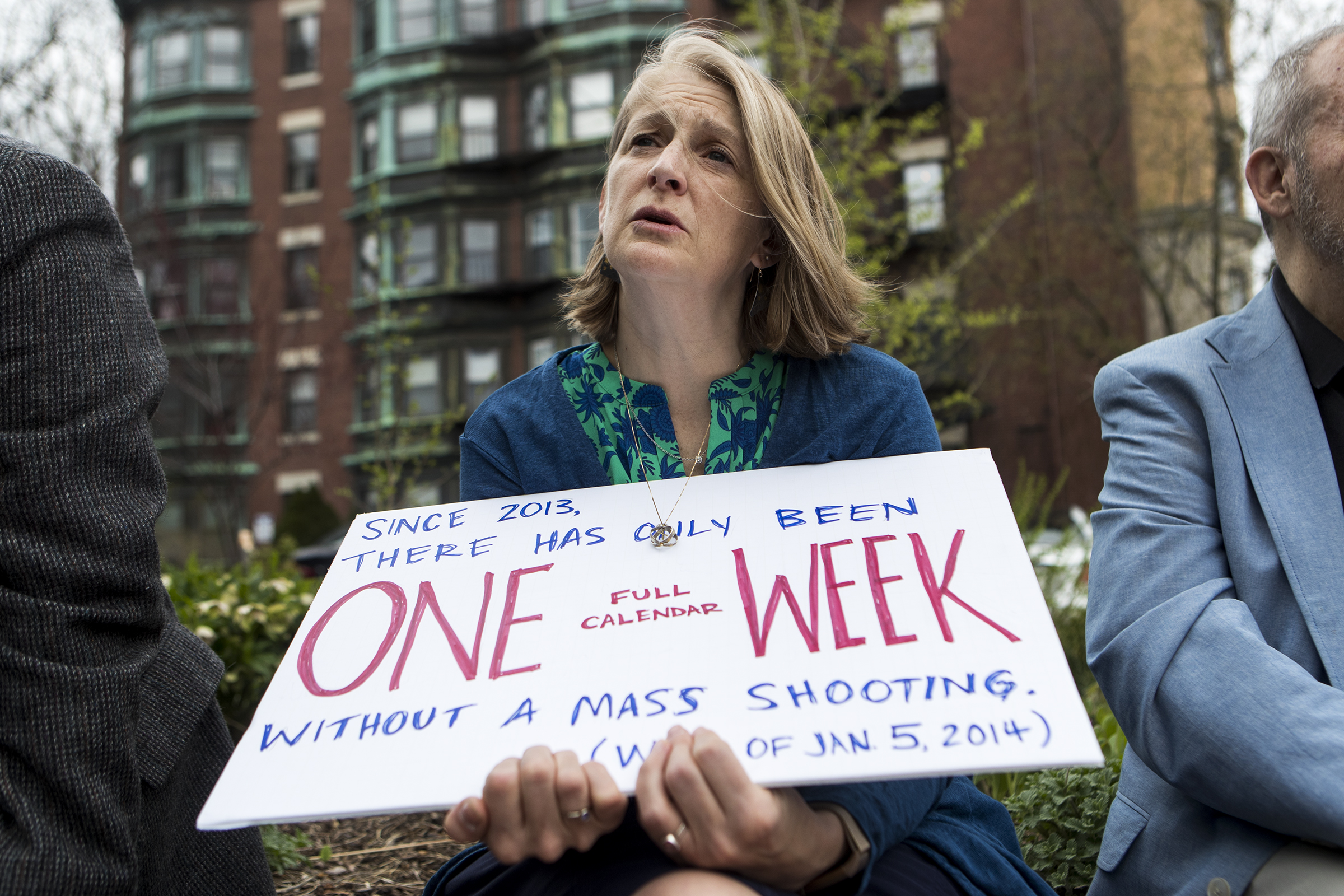 Kristin Griffin, of Cambridge, holds a sign while listening to the names of 2018 mass shooting victims at the Old Cambridge Baptist Church on April 19, 2019.