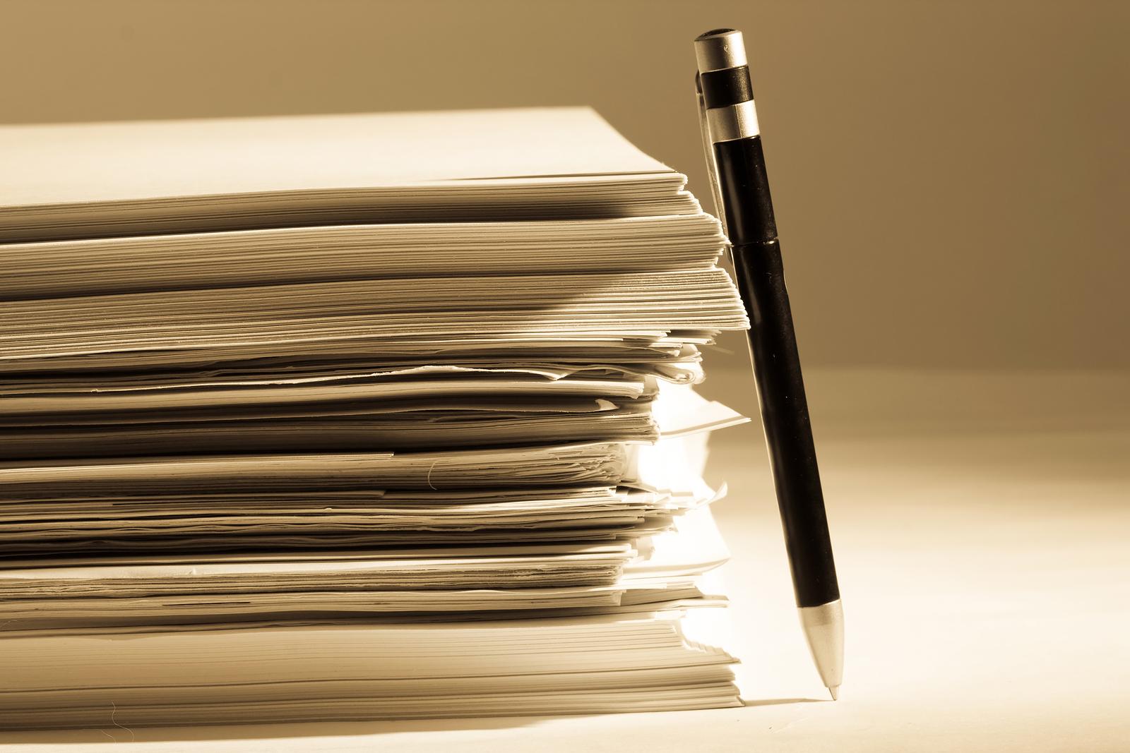 bigstock-a-pen-near-stack-of-paper-12931193.jpg