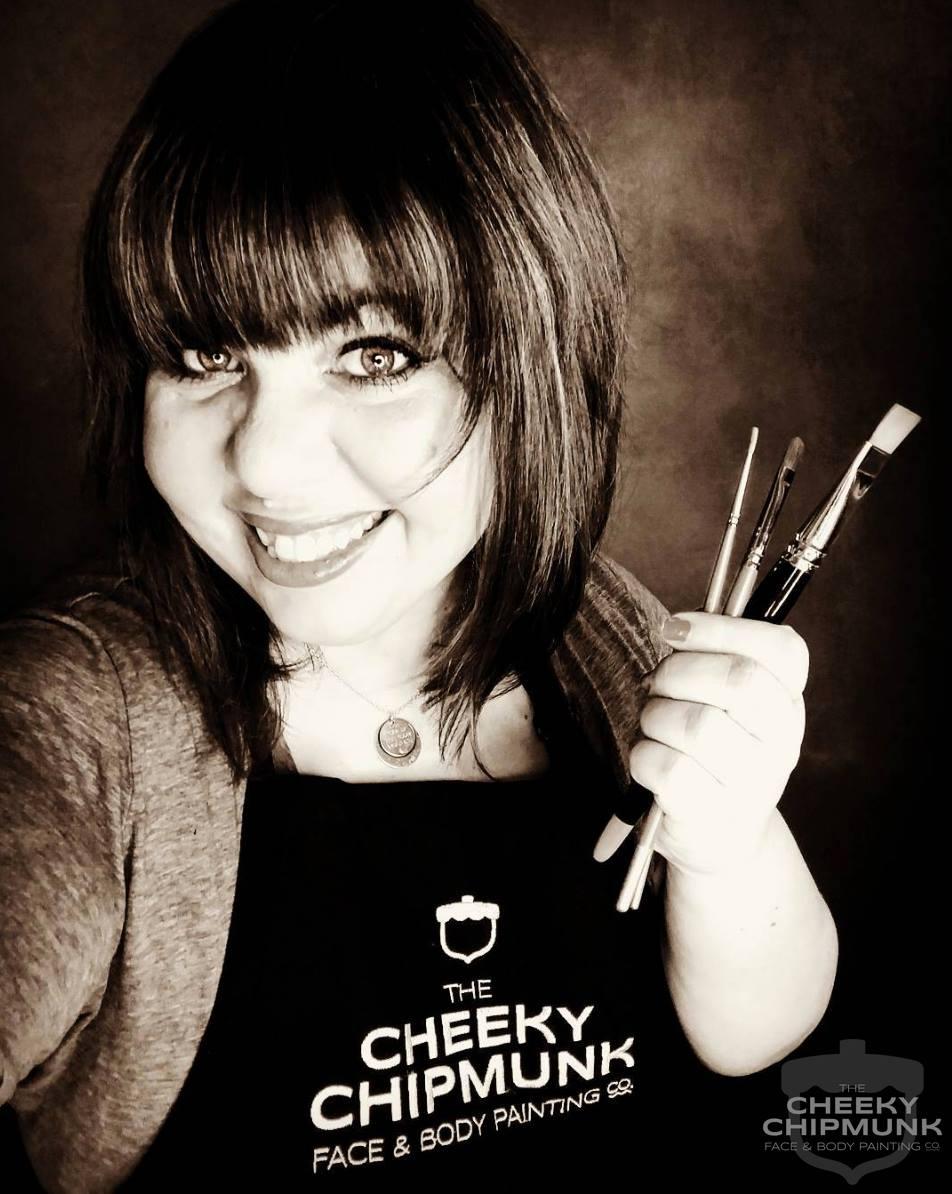 lenore-koppelman-the-cheeky-chipmunk-holding-paint-brushes-apron-black-and-white-headshot-selfie.jpg