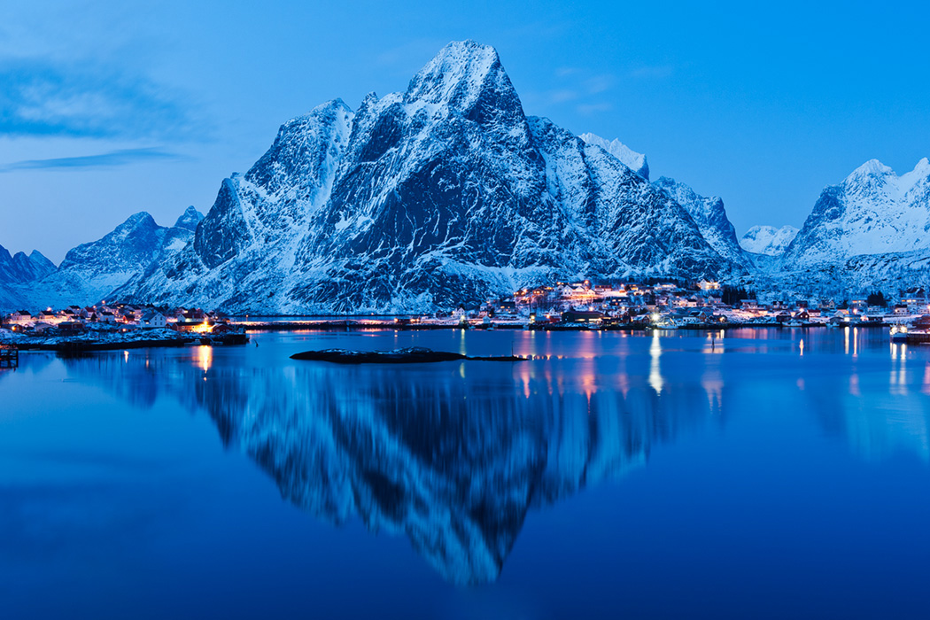 Reflection of Olstind mountain peak in harbour at Reine, Lofoten Islands, Norway