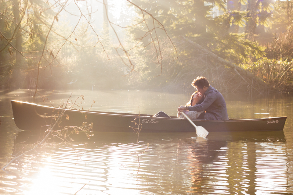 couple kissing on lake in canoe