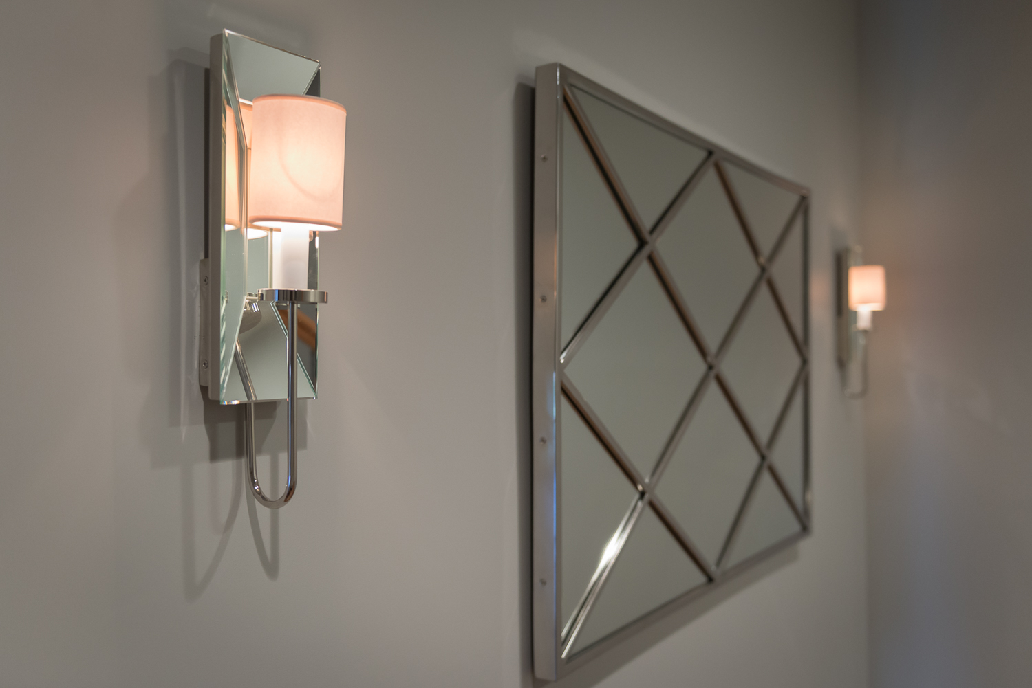 Sconces and mirror add some sparkle to the hallway into the basement. www.saranobledesigns.com