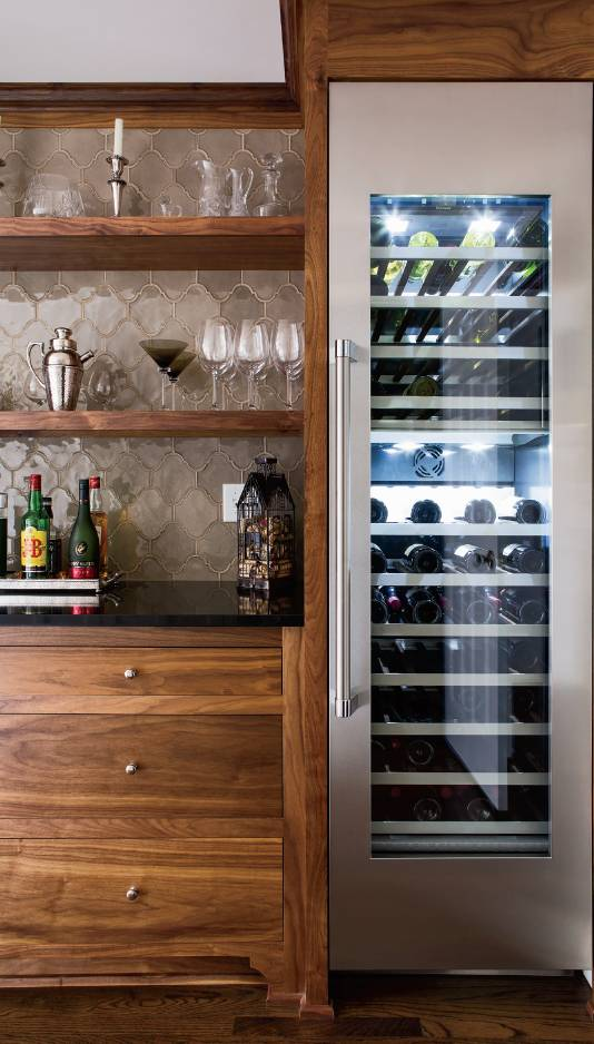 A walnut bar area was created that incorporated bar features and extra storage done in walnut custom cabinetry.