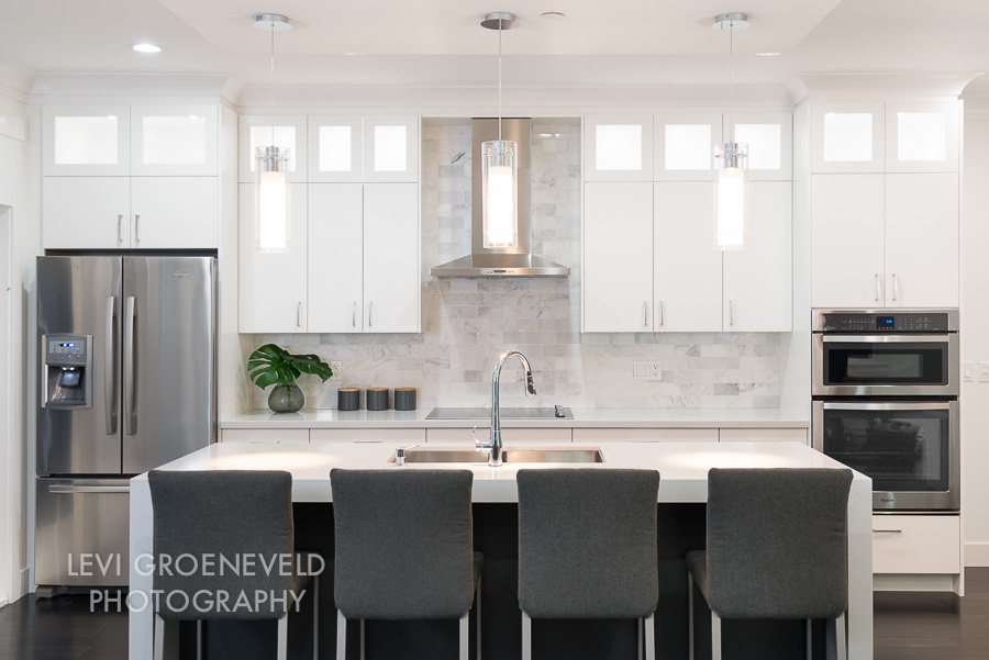 "The kitchen features a beautiful 3"" thick white quartz waterfall island countertop. We chose white carrara marble subway tile for the backsplash and added custom charcoal bar stools to add contrast."