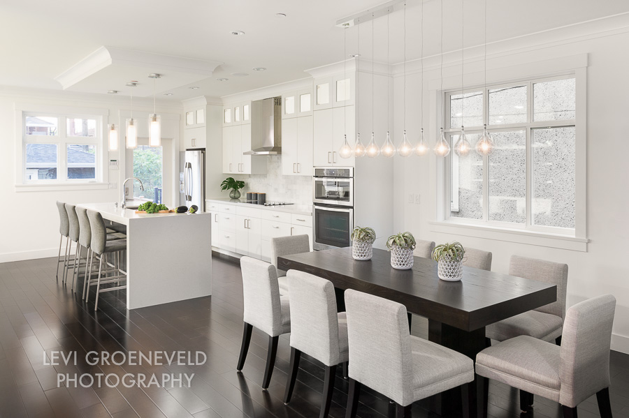 The open concept floor plan in the kitchen and dining room is the perfect set up for entertaining a group. Both rooms flow together with linear glass pendants and a continuing neutral palette.