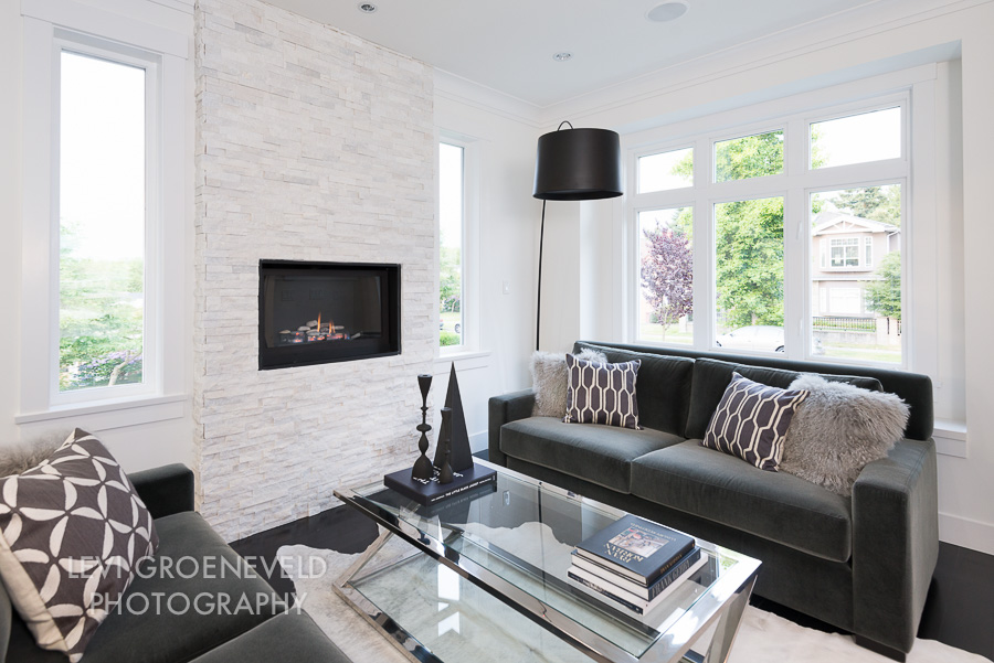 The living room features a floor to ceiling marble stone fireplace and a beautiful white cow hide rug to anchor the space. Custom sofas and Mongolian sheep fur pillows add softness and texture making it a comfortable area to relax and socialize.