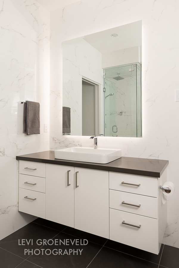 The modern master bathroom has clean lines with a floating countertop and backlit mirror. It features a beautiful grey quartz countertop and a square charcoal floor tile.