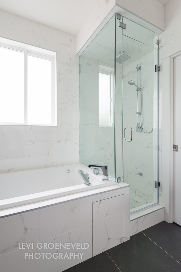 The other side of the master bathroom features a jacuzzi tub and steam shower for the ultimate relaxation. The wall tile is a beautiful faux white marble and covers three of the walls completely.