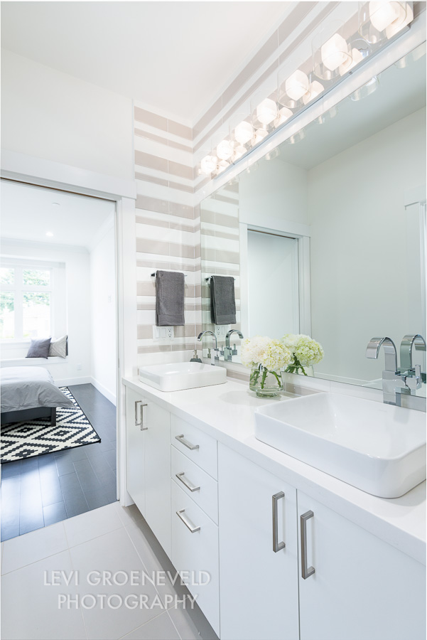 The shared bathroom joins the other two bedrooms with pocket doors on either side. We created a custom striped tile pattern on the walls around the double sinks to add interest and texture to the space.