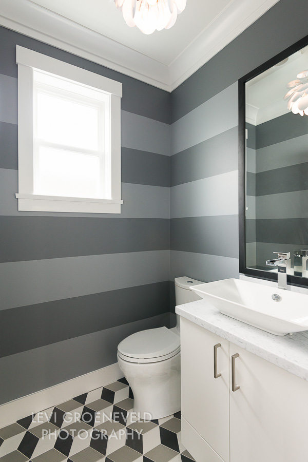 Powder rooms are fun because you can do something a little more creative with them. Nobody spends a lot of time in there so you might as well leave them with an impression. We decided to put a fun geometric floor and striped wall all while keeping the neutral palette of the house. The fun Marset pendant and carrara marble countertop add interest to the small space.