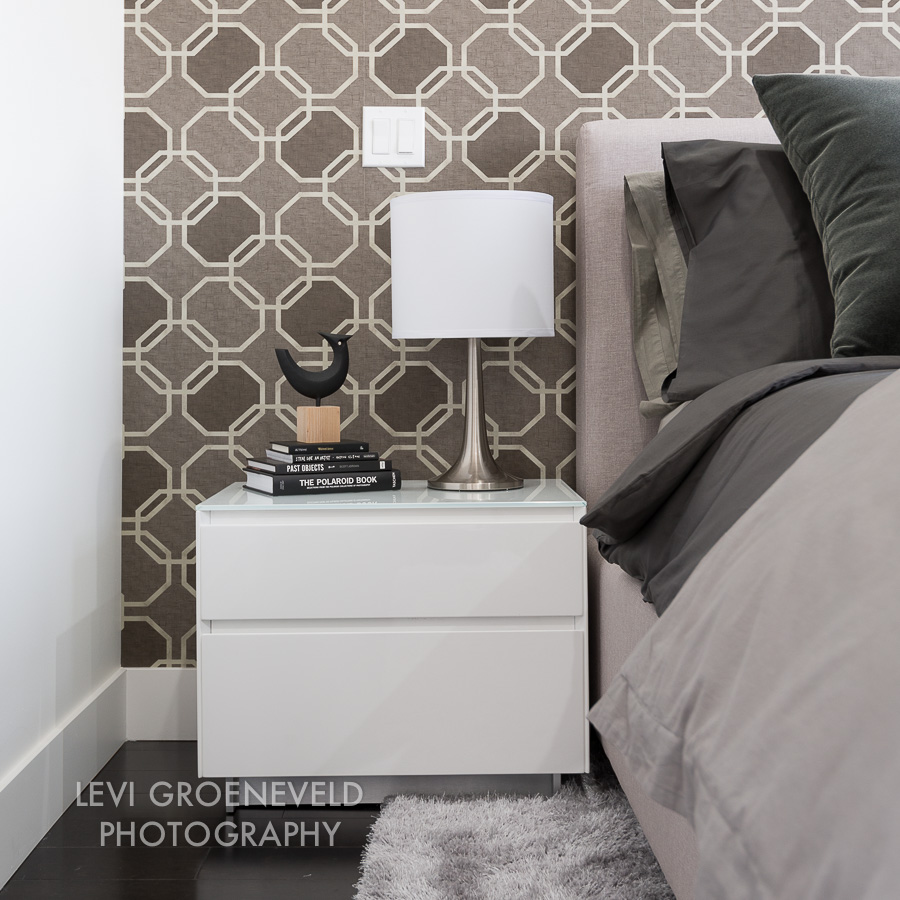 In the master bedroom we used a geometric wall covering as the focal point on the headboard wall. A cozy rug, upholstered headboard and deluxe bedding make for a space that is both comfortable and stylish.
