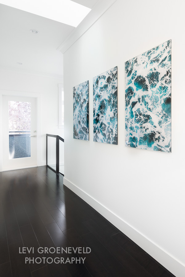 A white gallery wall in the hallway lends itself to perfectly host three beautiful pieces of art by  Levi Groeneveld . The pieces add a welcome pop of colour to the space.