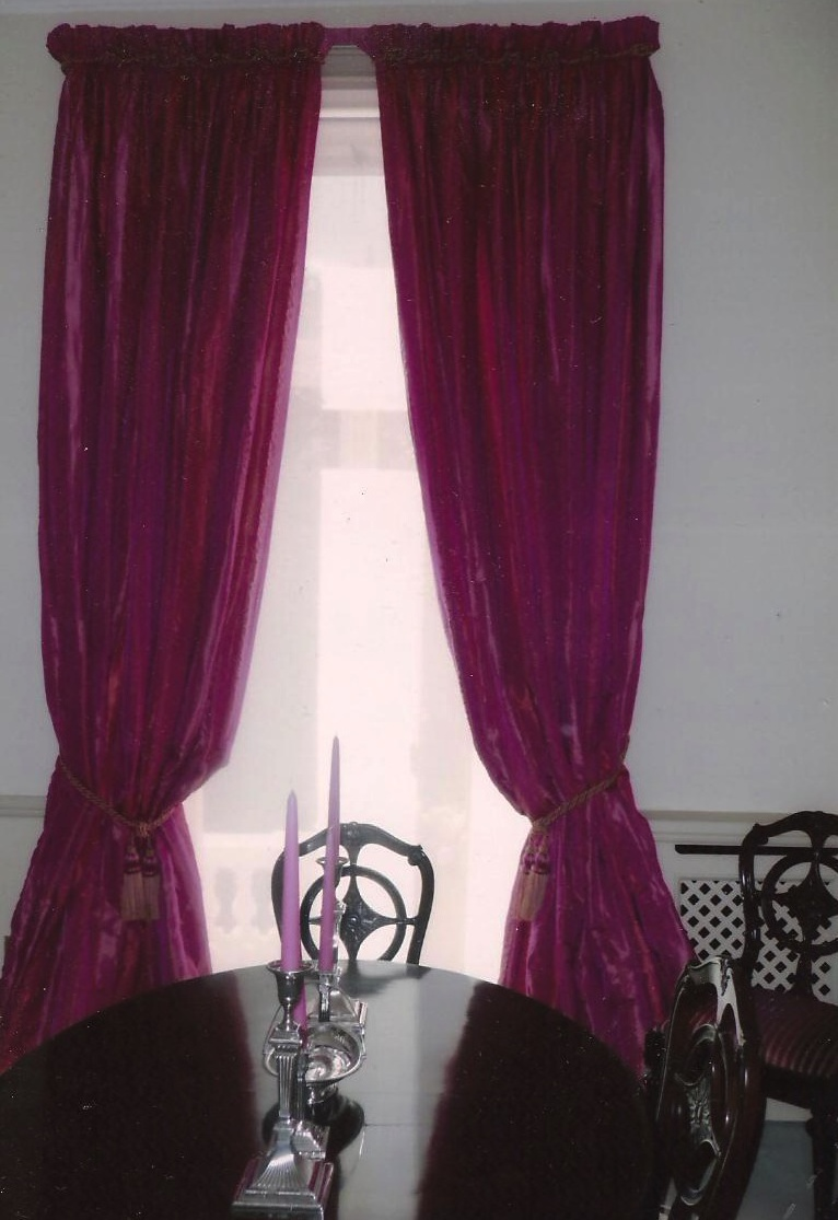 A rather bright pair of fuchsia pink curtains with rope trim and tassel tie backs and sheer roller blind in a town house in London