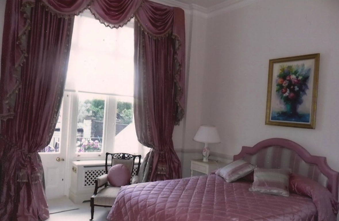 London- Dusty pink silk curtains with swags and tails. Matching quilted bedspread with pillow flap, shaped headboard and round cushion.