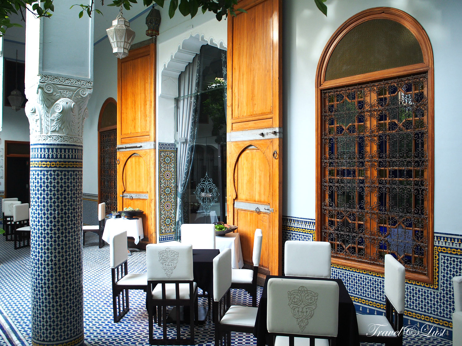 Eden restaurant with zellij tiles, carved woodwork and a view out onto the inner patio.