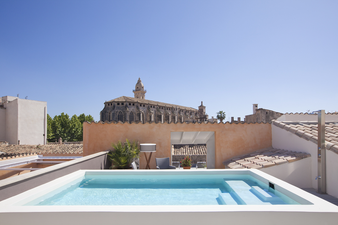 Heated rooftop pool area on the terrace with multiple sun loungers and seats to keep you comfy whilst sipping your favourite drink. Notice the Sant Francesc church in the background.
