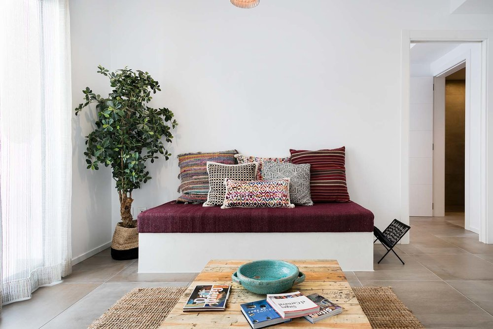 Spacious lounge area with colourful cushions, natural elements and books for you to enjoy.