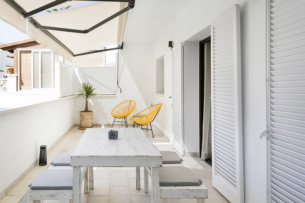 White washed outdoor area with pops of colour from those acapulco style chairs.
