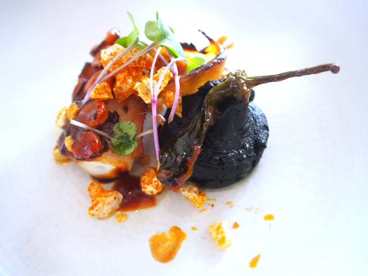 ''BBQ Octopus Causa'' - Roasted octopus, black (squid ink) mashed potato, roasted onion, pepper and pork rind.