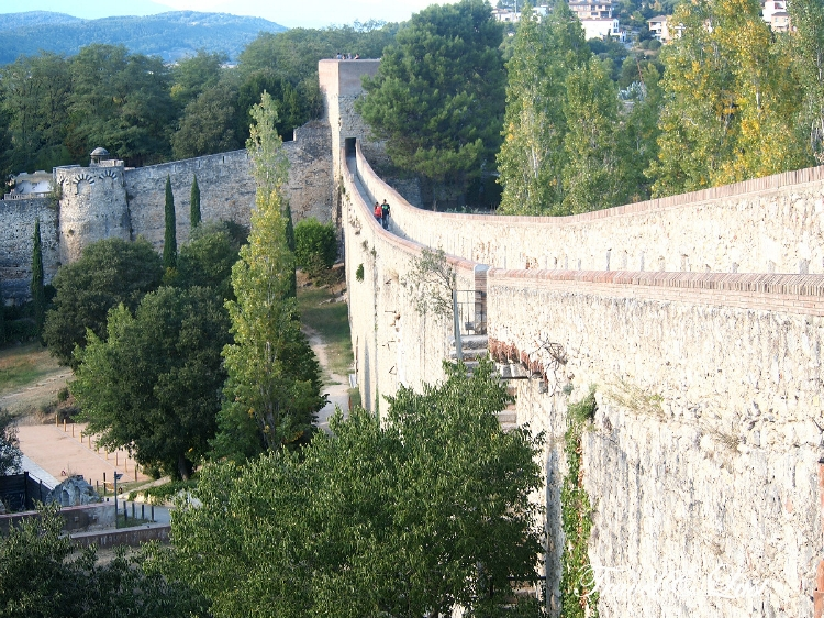 Walking up the old city walls surrounding the city. The extension of the Roman walls during the medieval ages today enables visitors to stroll along this walkway.