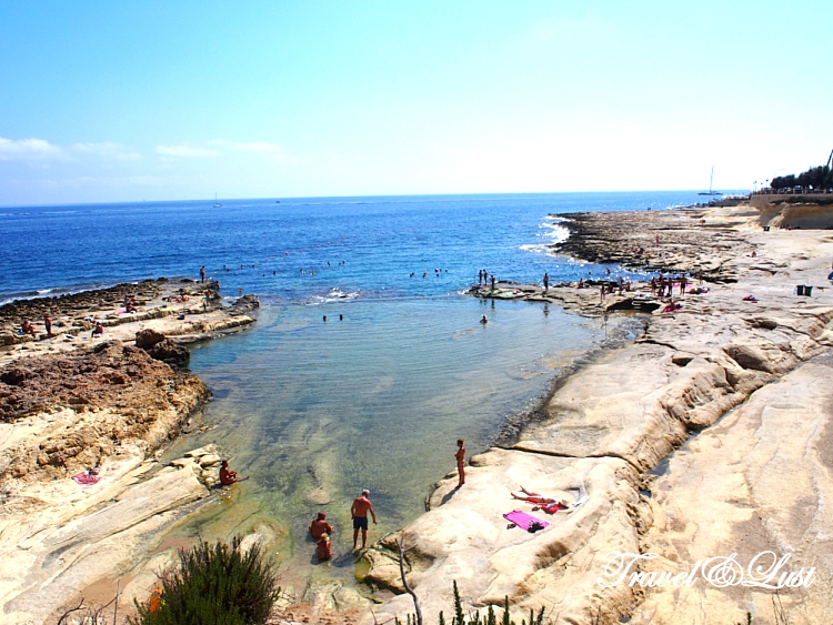 People swimming and sun bathing on the rocks at Sliema.