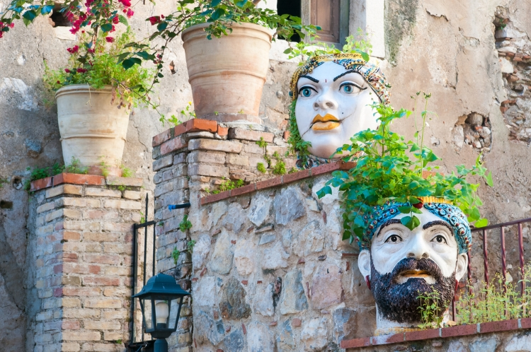 Traditional ceramic head shaped planters set into the stone of a wall along the streets of Taormina.