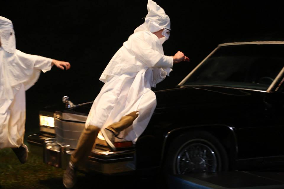 Some Klansmen jump on the hood to simulate being run over.