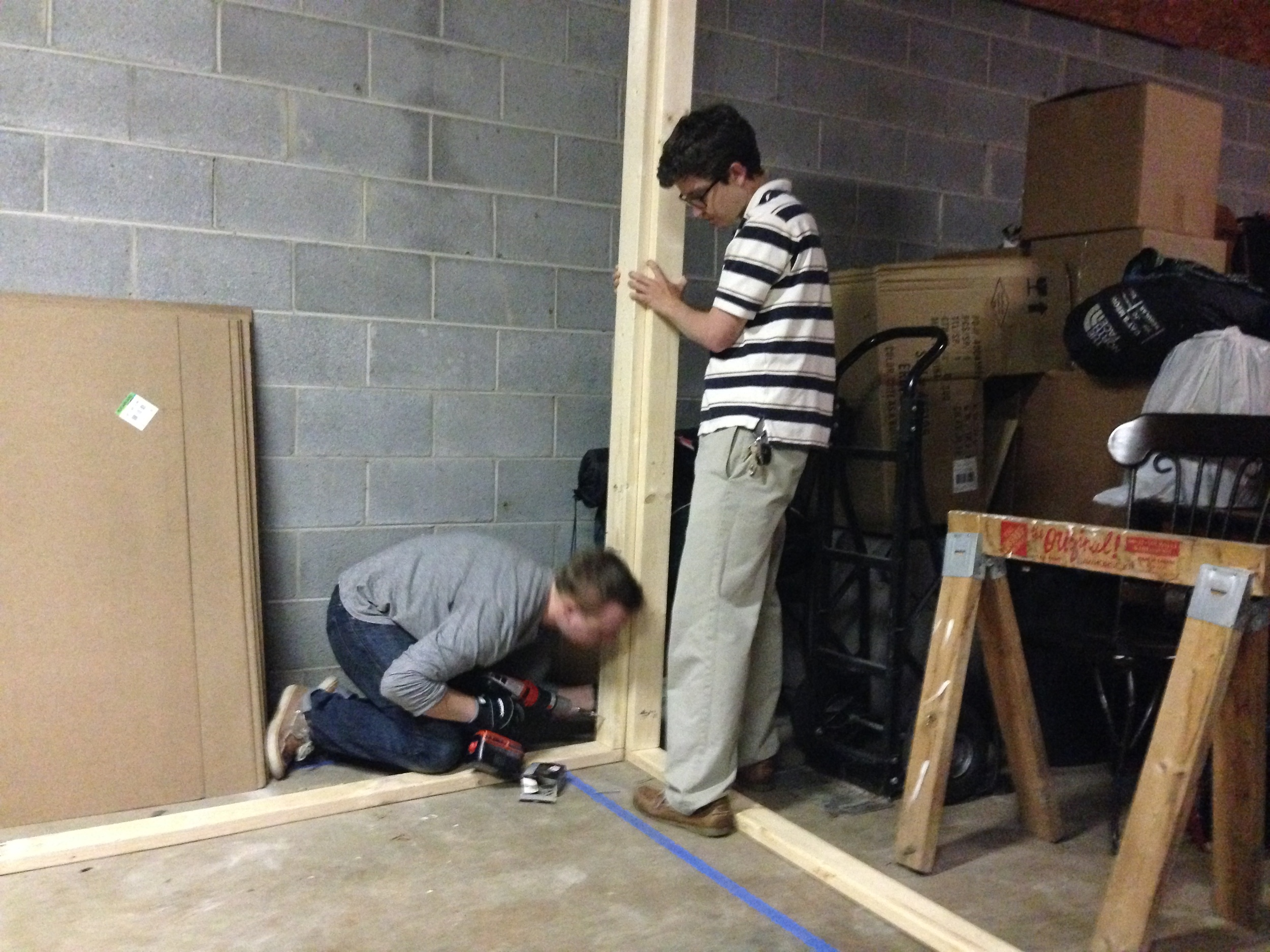 Ben and Ryan assemble a wall for the embalming room set.