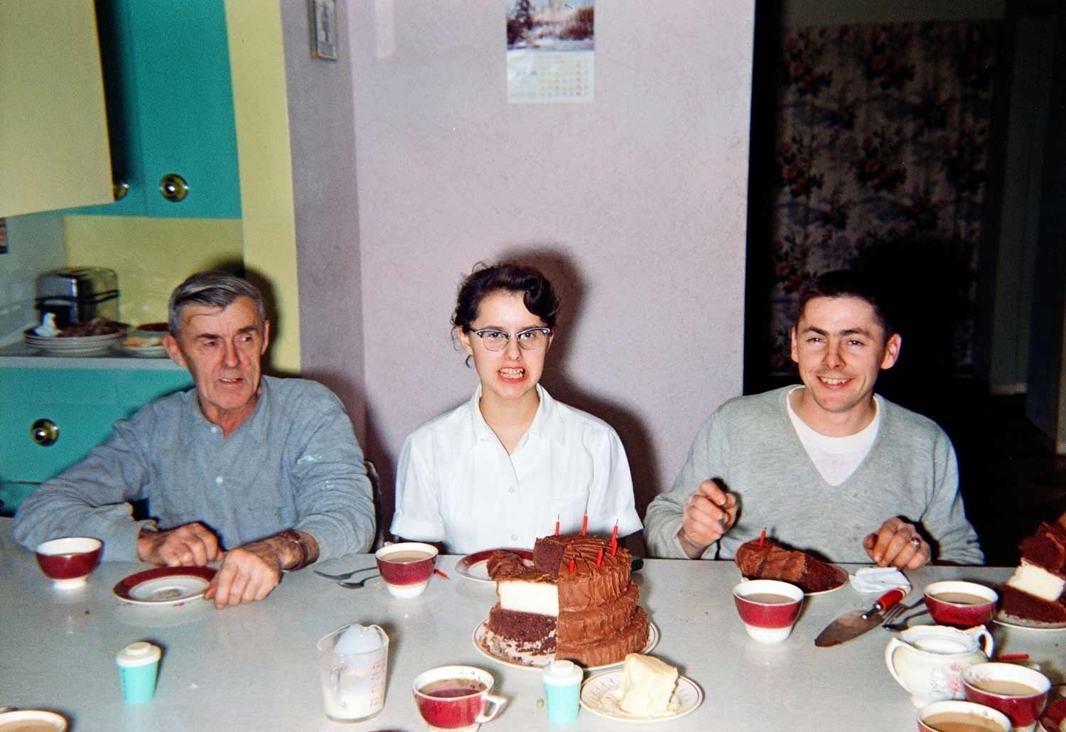 Some family members enjoy a slice of the towering cake.