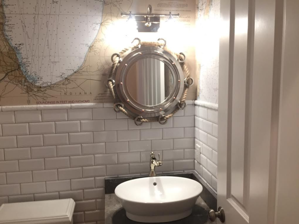 Subway Tile makes a nice surface in a bathroom. Note the bottom part of Lake Michigan above the cap and decorative nautical decor.