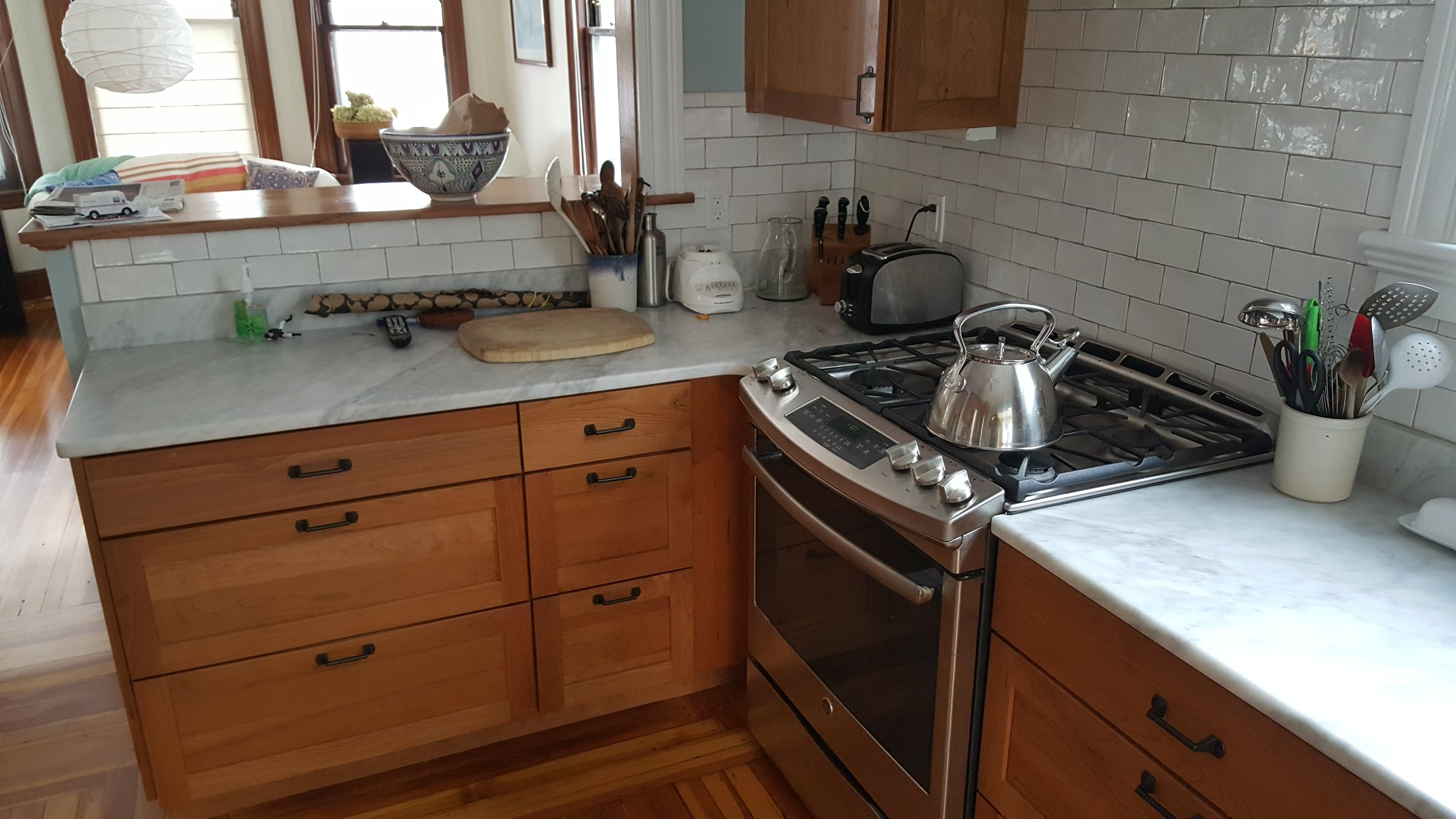 Touchstone Cherry Cabinets, White Carrara Top, irregular subway tile, grey grout. The chimney was right in front of you.