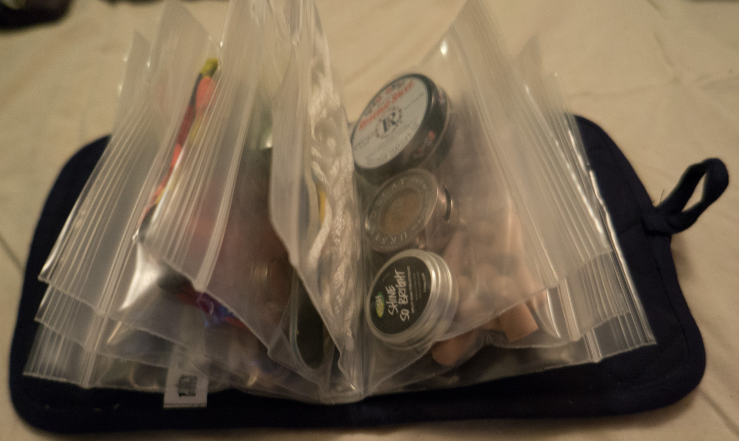 """Beth's """"Bag of Awesome""""  Contains sewing kit, safety pins, earplugs, lip balm, eye shadow, pomade, string, rubber bands, scissors, mini cuticle cutter, nail file, tweezers, buff bandana, concealer, q-tips, hair bands."""