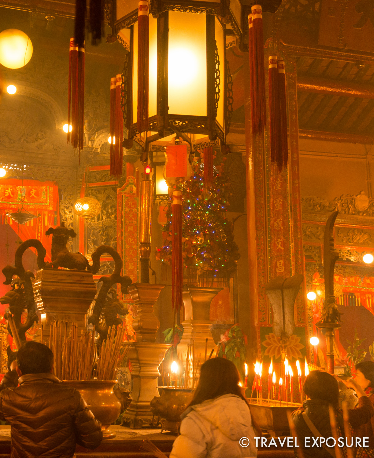 Inside the Man Mo temple, worshippers light incense sticks and place them in bronze urns to bring good fortune.