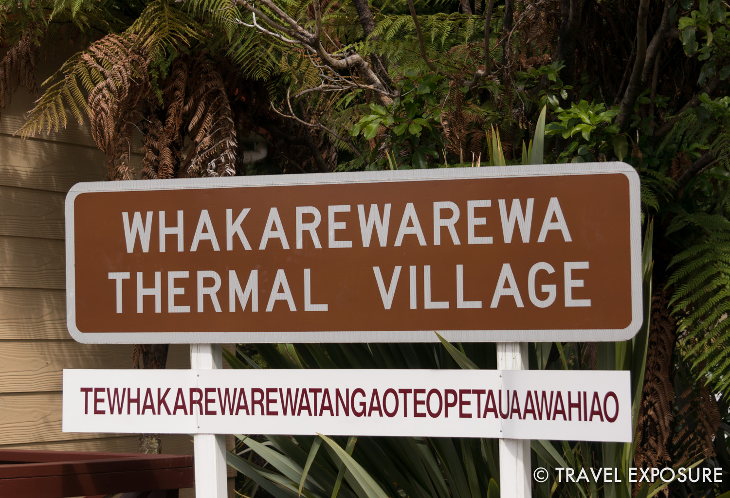 The sign below lists the full Maori name of the village