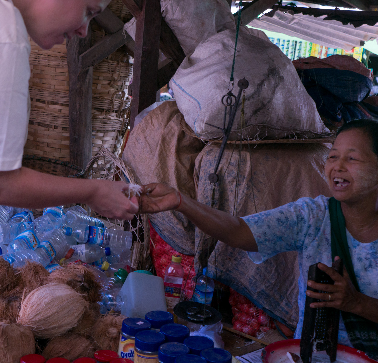 A nice woman in the market at Inle Lake handing me a sample of a flan-like desert.
