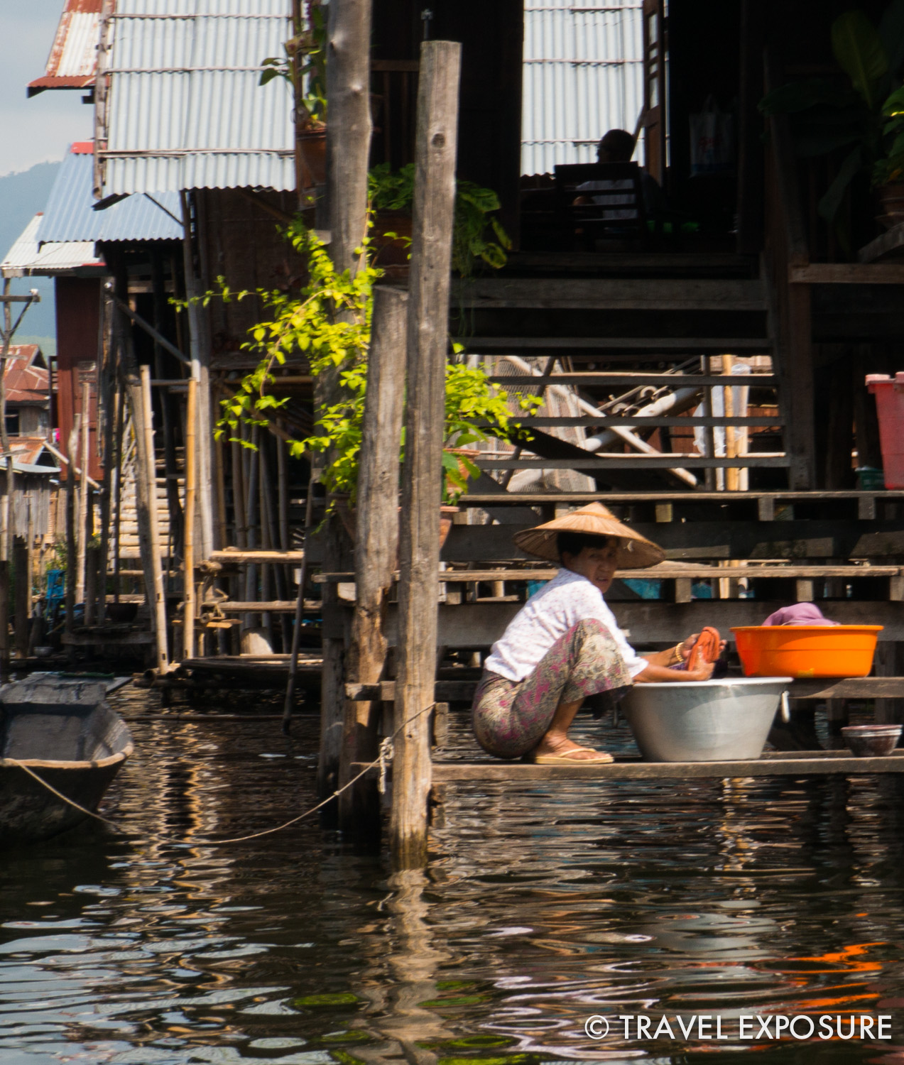 A woman washes clothes outside her house in Inle Lake, Myanmar
